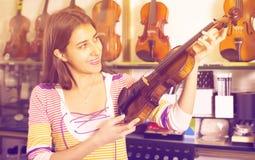 Flickan som väljer fiolen i musik, shoppar Arkivfoto