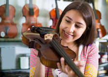 Flickan som väljer fiolen i musik, shoppar Arkivbild