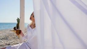 Flickan som vilar på stranden som dricker kokosnötfruktsaft, härligt kvinnasammanträde i bungalow med vit, hänger upp gardiner på arkivfilmer