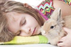 Flickan sover med kaninen royaltyfri fotografi