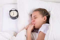 Flickan sover och suger hennes tumme, en vana efter barndom arkivfoto