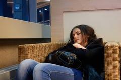 Flickan sover sammanträde i en vide- wood stol, medan vänta på avvikelse royaltyfri bild