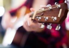 Flickan spelar den akustiska gitarren Fokus på huvudet av gitarren Arkivbild