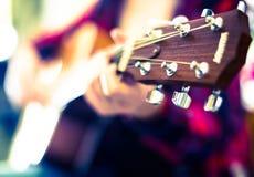 Flickan spelar den akustiska gitarren Fokus på huvudet av gitarren Fotografering för Bildbyråer