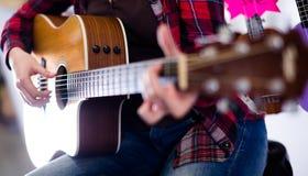 Flickan spelar den akustiska gitarren Fokus på kropp av gitarren Fotografering för Bildbyråer