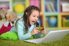 Flickan spelar en dataspel Royaltyfri Fotografi