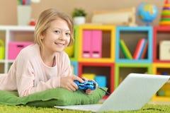 Flickan spelar en dataspel Arkivfoton