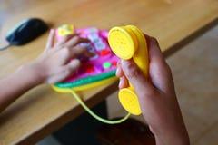 Flickan spelar en leksaktelefon Royaltyfri Bild