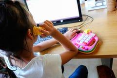 Flickan spelar en telefon och leker med datoren royaltyfria bilder