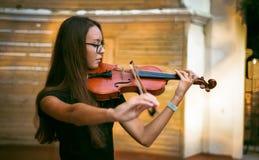 Flickan spelar fiolen Arkivfoton