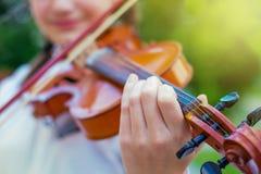Flickan spelar fiolen mot bakgrunden av nature_ royaltyfri fotografi