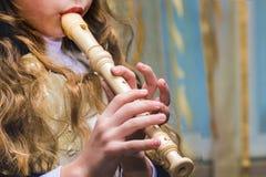 Flickan spelar flöjten, räcker tätt upp arkivbild