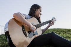 Flickan spelar gitarren Fotografering för Bildbyråer