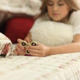 Flickan spelar hemma med rastlös människaspinnare i händer, begreppet av den befriande spänningen, framkallar en liten handmatema Royaltyfria Bilder
