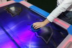 Flickan spelar lufthockeyleken och rymmer slagmannen Klubbor och puck i händer Violett tabell med modellen Lek i underhållning royaltyfri foto