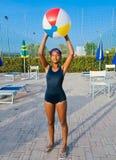 Flickan spelar med bollen i pölen på solnedgången royaltyfria bilder
