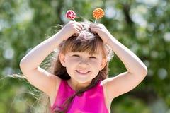 Flickan spelar med stora sötsaker på en pinne royaltyfria foton