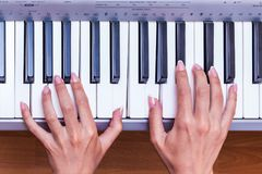 Flickan spelar pianot Händer av en kvinna med utsökt manicu fotografering för bildbyråer