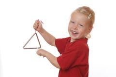 Flickan spelar triangeln Arkivfoton