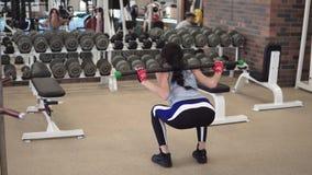Flickan squats i idrottshallen med en skivstång stock video