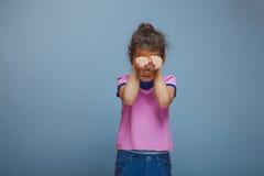 Flickan stängde henne ögonhänder på en grå bakgrund Royaltyfria Bilder