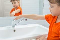 Flickan stängde vattnet från blandare, når han har tvättat sig royaltyfri bild