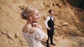 Flickan står bredvid hennes unga man på bakgrunden av sandkullar Hon ser från kameran till hennes pojkvän lager videofilmer