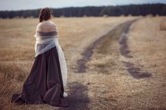 Flickan står i fältet vid vägen Royaltyfria Foton