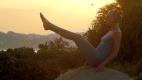 Flickan står i navasana på stort vaggar på soluppgångultrarapid arkivfilmer