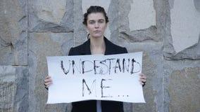 Flickan står med ett tecken lager videofilmer