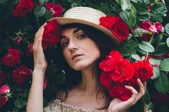 Flickan står mot buskar för en bakgrund med röda rosor Royaltyfria Bilder