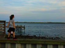 Flickan står mot vind på kust arkivbild