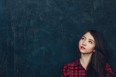Flickan står nära väggen i studion Arkivfoto