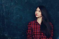 Flickan står nära väggen i studion Arkivfoton