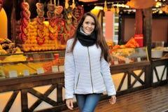 Flickan står på bakgrunden av jul shoppar med Royaltyfria Foton