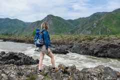 Flickan står på banken av en bergflod Arkivfoto