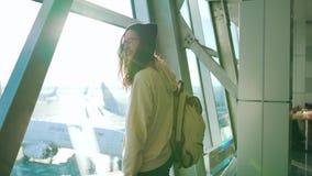 Flickan står på fönstret i flygplatsterminal stock video