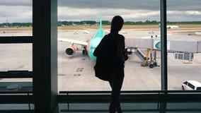 Flickan står på fönstret i flygplatsterminalen lager videofilmer