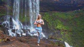 Flickan står på vänstra benveck gömma i handflatan i bön vid vattenfallet lager videofilmer