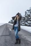 Flickan står på vintervägen royaltyfri bild