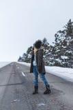 Flickan står på vintervägen royaltyfria foton