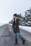 Flickan står på vintervägen arkivbilder