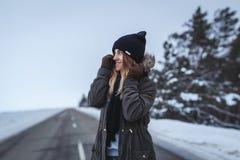 Flickan står på vintervägen arkivbild