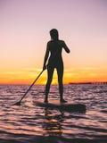 Flickan står upp skovellogi på skymning på ett plant varmt tyst hav med solnedgångfärger Royaltyfri Foto