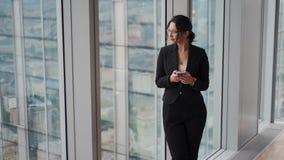 Flickan står vid fönstret på det höga golvet av en skyskrapa Stående av en attraktiv affärskvinna med en smartphone stock video