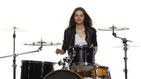 Flickan startar att spela driftig musik, henne gyckel, leenden Vit bakgrund arkivfilmer