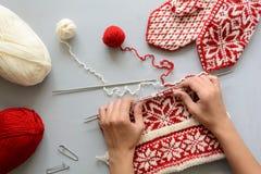 Flickan sticker röda och vita jacquardhattstickor på grå träbakgrund Process av handarbete arkivbilder