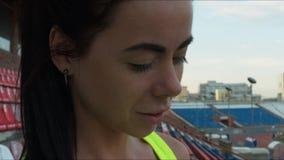 Flickan stirrar på telefonen på en stadion och le för sportar Närbild arkivfilmer