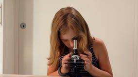 Flickan studerar en glidbana under ett mikroskop arkivfilmer