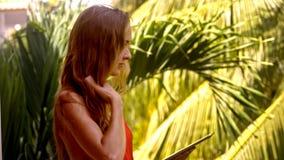 Flickan surfar internet som använder minnestavlan mot, gömma i handflatan lager videofilmer